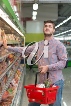 Handsome Young Man Shopping For Meat And Fish In Produce Department Of A Grocery Store - Supermarket - Shallow Deep Of Field