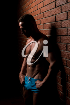 Portrait Of A Young Physically Fit Man Showing His Well Trained Body - Muscular Athletic Bodybuilder Fitness Model Posing After Exercises On Wall of Bricks
