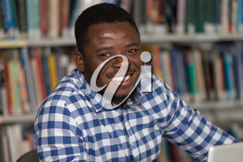 Portrait Of African Clever Student With Open Book Reading It In College Library - Shallow Depth Of Field