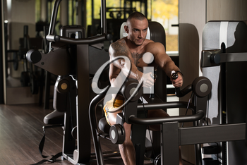 Handsome Bodybuilder Doing Heavy Weight Exercise For Back On Machine