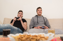 Two Young Brothers Having Happy Time Together Playing Video Games At Home