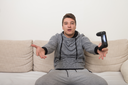 Young Gamer Sitting On Sofa And Playing Video Games At Home
