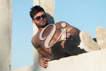 Handsome Man Standing Strong and Posing at Outdoors Wearing Black Jeans - Background of Sky