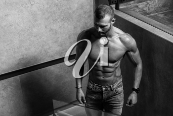 Portrait of a Young Physically Fit Man Showing His Well Trained Body While Wearing Blue Jeans - Muscular Athletic Bodybuilder Fitness Model Posing After Exercises on Wall Near the Wall - a Place for Your Text