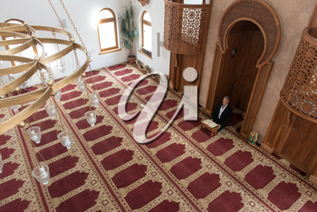 Businessman Muslim Is Reading The Koran Making Traditional Prayer to God Allah in the Mosque