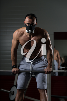 Bodybuilder Doing Push Ups On Barbell As Part Of Bodybuilding Training In Elevation Mask