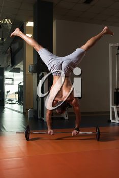 Bodybuilder Doing Handstand Push Ups On Barbell As Part Of Bodybuilding Training In Gym