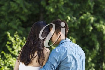 Horizontal photo of a young adult couple touching forehead to forehead with green trees in background