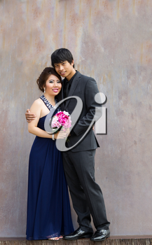 Vertical photo of young adult couple holding a bouquet of flowers, in between them, as they hug each other with rustic metal wall in background