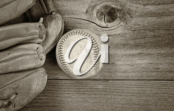 Vintage concept of old baseball and mitt on rustic wood. Layout in horizontal format. Slight vignette on border.