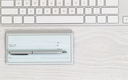 Image of partial keyboard with blank checkbook and silver pen on white desktop. Layout in horizontal format.