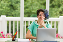 Smiling teen girl, looking forward, with computer, books and pencils in forefront. Large windows in background with blurred out bright green trees and flowers.