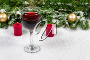 Close up of a glass of red wine with burning red candles, evergreen branches and gold ornaments covered in snow. Selective focus on front upper part of wine glass with holiday concept.