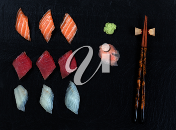 Overhead view of fresh Japanese sushi, ginger, wasabi, and chopsticks on black slate.