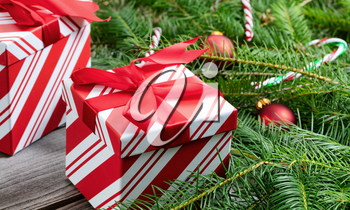 Close up of a boxed gift with Christmas tree branches and ornaments in background