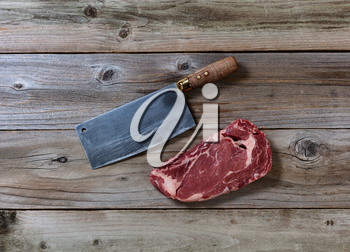 Fresh Raw Prime Beef Steak and Butcher Knife on rustic wooden boards
