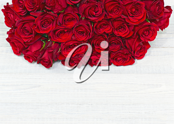 Colorful flower bouquet from red roses on white wooden background. Closeup.