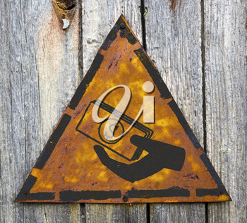 Royalty Free Photo of a Hand Giving Money on a Rusty Sign Against a Wooden Wall