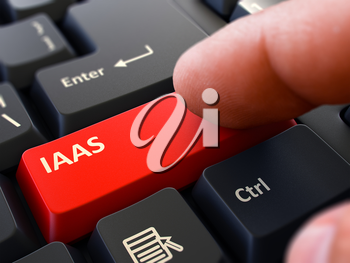 IAAS -  Infrastructure as a Service - Written on Red Keyboard Key. Male Hand Presses Button on Black PC Keyboard. Closeup View. Blurred Background.