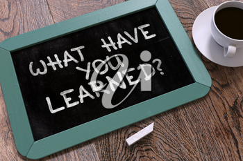 What Have You Learned? Motivational Quote Hand Drawn on Blue Chalkboard on Wooden Table. Business Background. Top View.