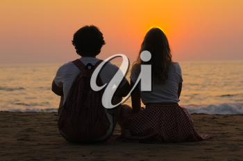 The young couple sitting on a sea beach and watching the beautiful sunset.