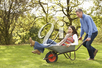 Couple With Man Giving Woman Ride In Wheelbarrow