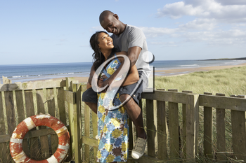 Romantic Young Couple Standing By Wooden Fence Of Beach Hut Amongst Dunes