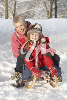 Young Girl With Grandmother Riding On Sledge In Snowy Landscape