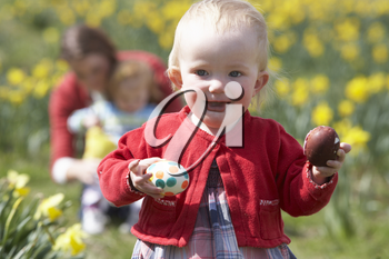Mother And Children In Daffodil Field With Decorated Easter Eggs