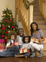 Young African American family with Christmas tree and gifts