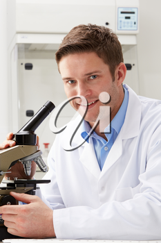 Portrait Of Scientist With Microscope In Laboratory