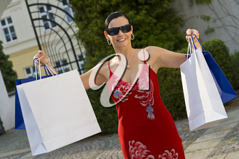 A classically beautiful Mediterranean woman holding up full shopping bags and looking very pleased with her purchases