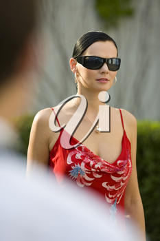 Shot of a beautiful mediterranean woman photographed over the shoulder of a man watching her walk by
