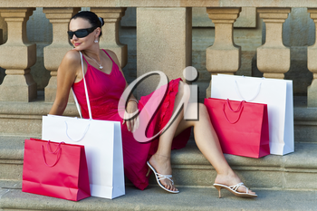 A classically beautiful latina woman in a red dress sitting with red and white shopping bags and looking happy