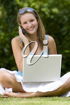 A beautiful young woman cross legged in a grassy sunlit setting, working on her laptop and chatting on her mobile phone