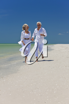 Happy senior man and woman couple running, laughing and holding hands on a deserted tropical beach with bright clear blue sky