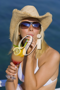 Stunningly beautiful young blond woman in straw cowboy hat and sunglasses enjoying a cocktail by a deep blue sea