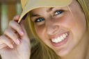A beautiful young lady with blonde hair and blue eyes tips her baseball cap to the camera while bathed in sunshine.