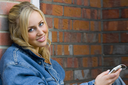 A beautiful young woman leaning againsat a wall and listeningto an mp3 player