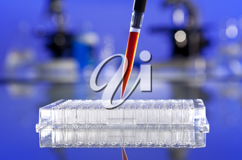A pipette full of blood sample or red liquid and cell tray in a laboratory environment with microscopes and other equipment out of focus in the background