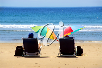 A couple relaxing on a beach under colorful umbrellas