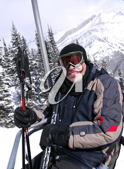 Happy man on a chairlift at downhill ski resort