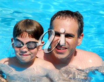 Father and son having fun in a swimming pool