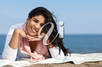 Portrait of beautiful smiling native american girl laying at beach