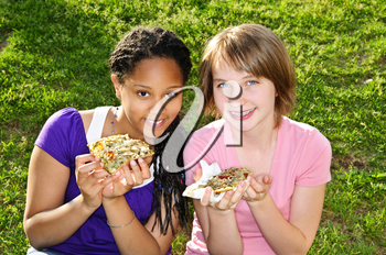 Two teenage girls sitting and eating pizza