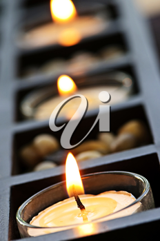 Burning candles in glass holders and wooden stand
