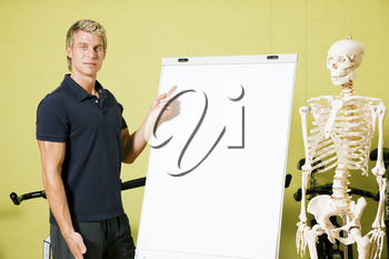 Fitness trainer in a gym explaining basic anatomy using a skeleton