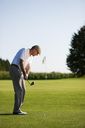 Senior golfer doing a golf stroke, he is playing on a wonderful summer afternoon