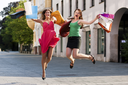 Two women being friends shopping downtown with colorful shopping bags, they are jumping for joy�
