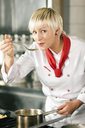 Female chefs in a restaurant or hotel kitchen cooking delicious food, tasting the half finished dish with a spoon